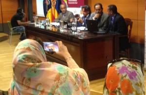 Dos mujeres con melfas sacan fotos a la mesa presidencial del foro Dajla-Canarias. (Foto MN).